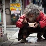 A homeless man in the back streets of Shibuya tucking in to a bowl of noodles